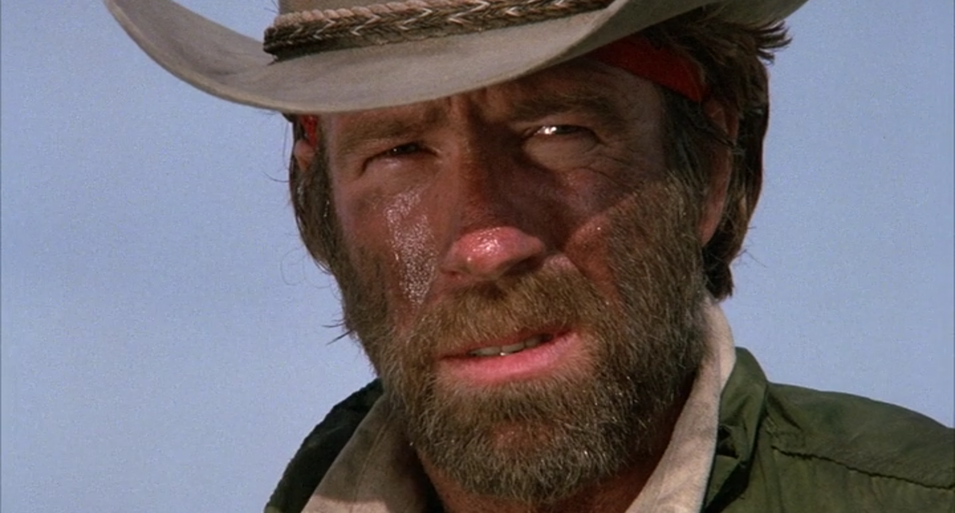 Close up of Chuck Norris as J.J. McQuade. Head only, in cowboy hat, full beard, and very dirty.