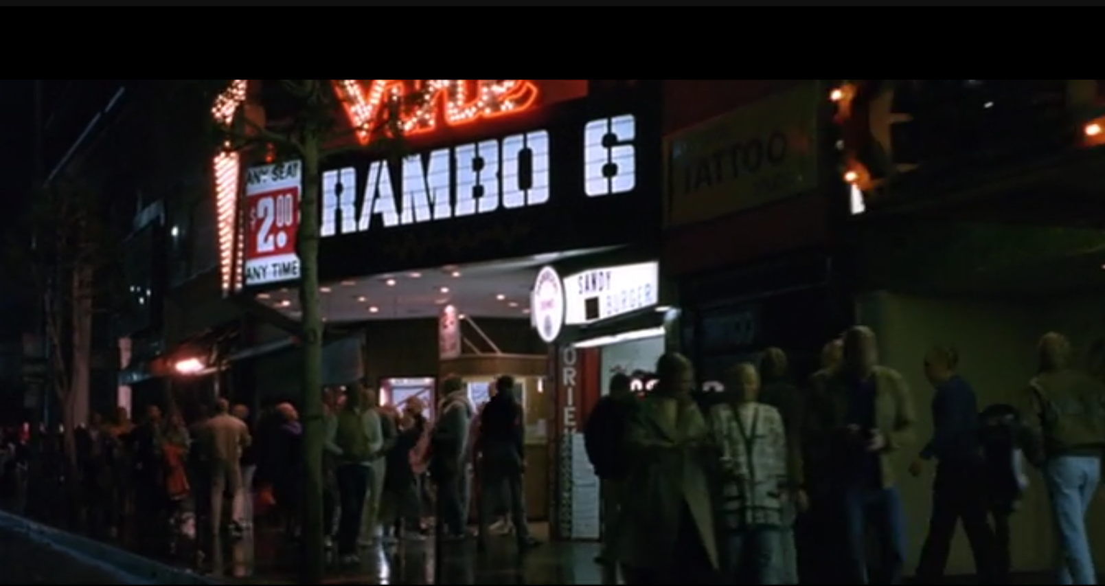 """A theater marquee with """"Rambo 6"""" in large bold letters while many people stand around the ticket counter."""
